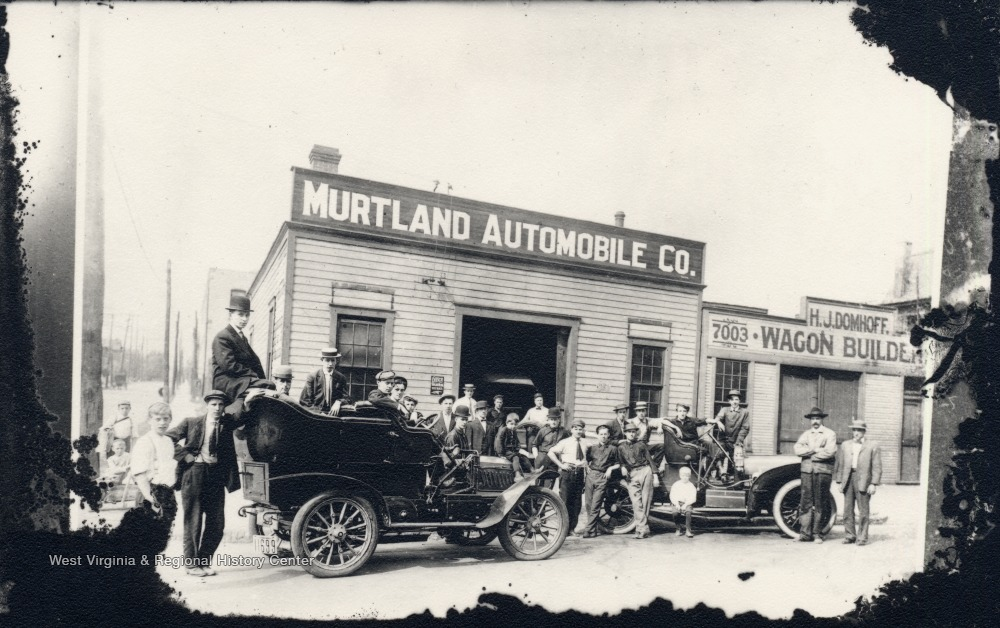 "Exterior of Murtland Automobile Company; people and automobiles are in front; also includes storefront of ""H.J. Domhoff, Wagon Builder."""