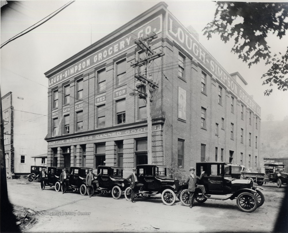 Exterior of Lough-Simpson Grocery Company; employees with company automobiles are in front.<br />