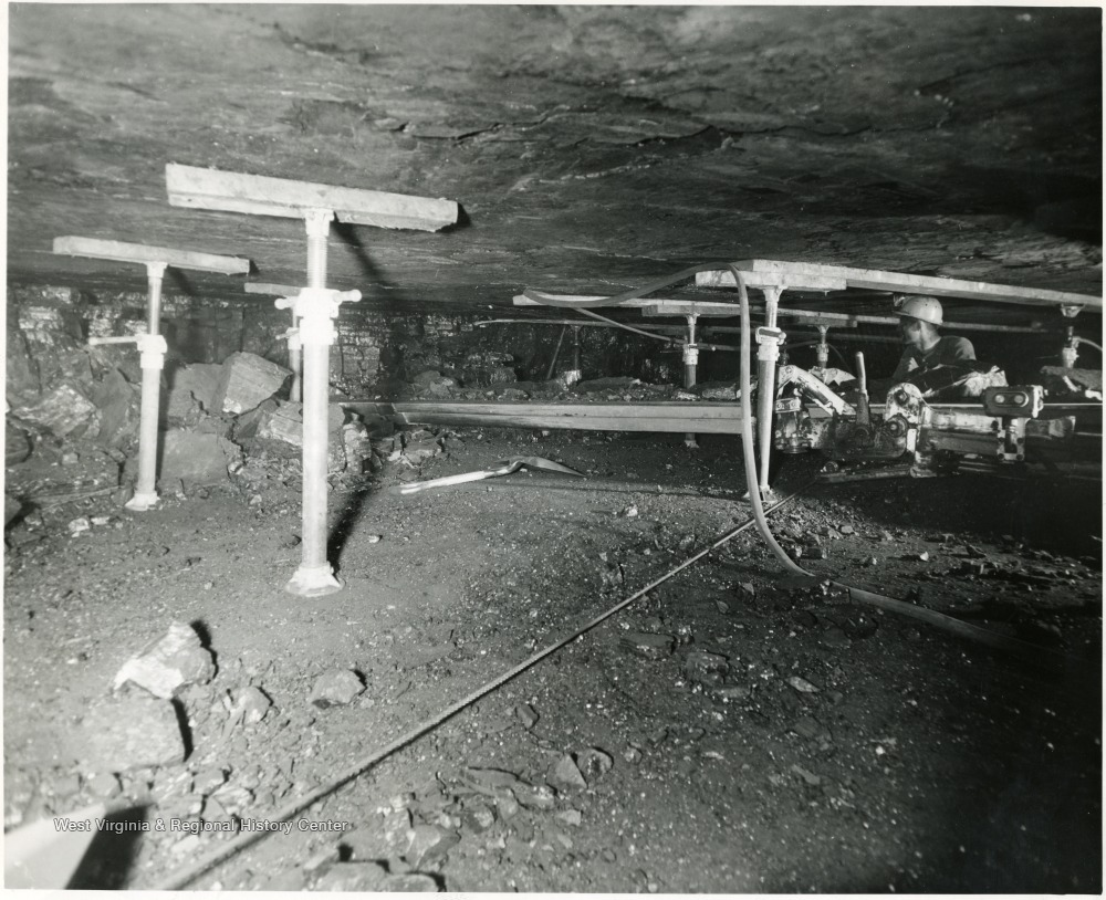 Man cutting coal in Consol. Coal Co. Mine in Kentucky. Note the roof supports using jacks.