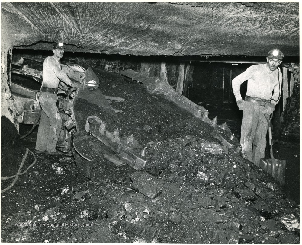 Two miners operating a loading machine.