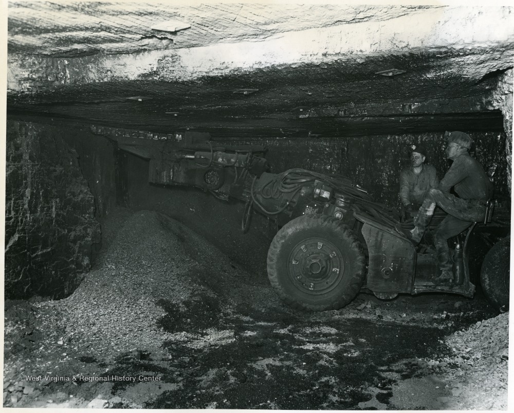 Two miners work with a cutting machine at Pursglove No. 15.