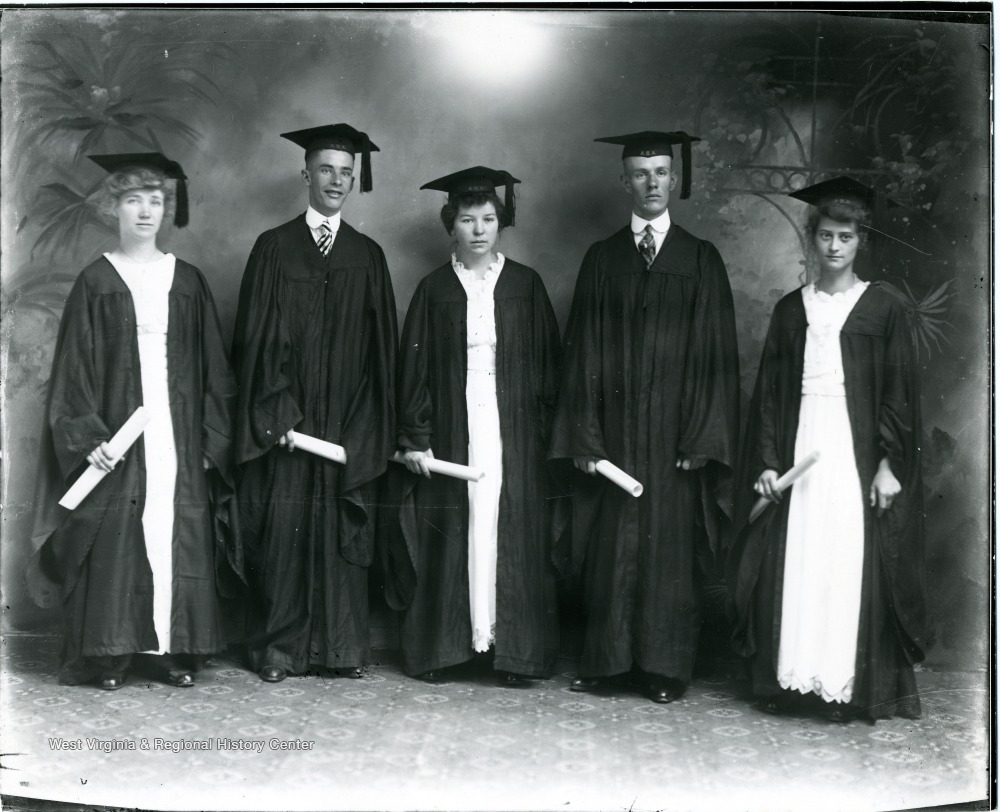 Group portrait of five graduates in caps and gowns.