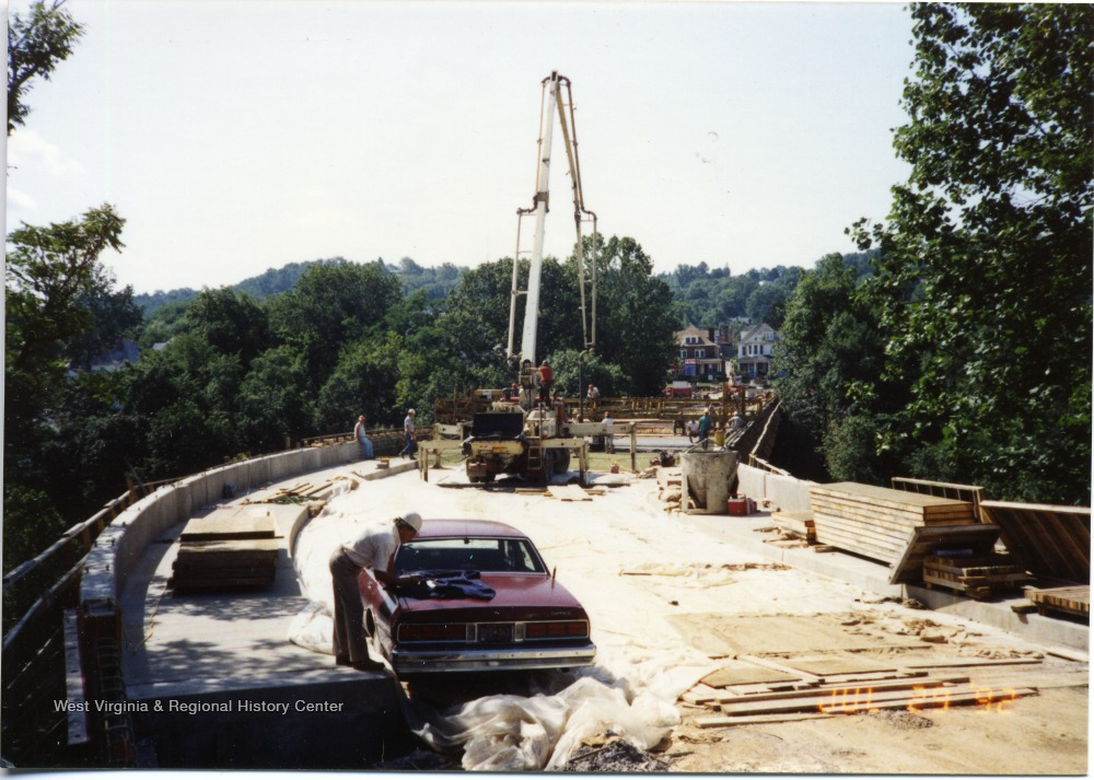 Unfinished bridge can be seen in progress. Workers surround equipment.