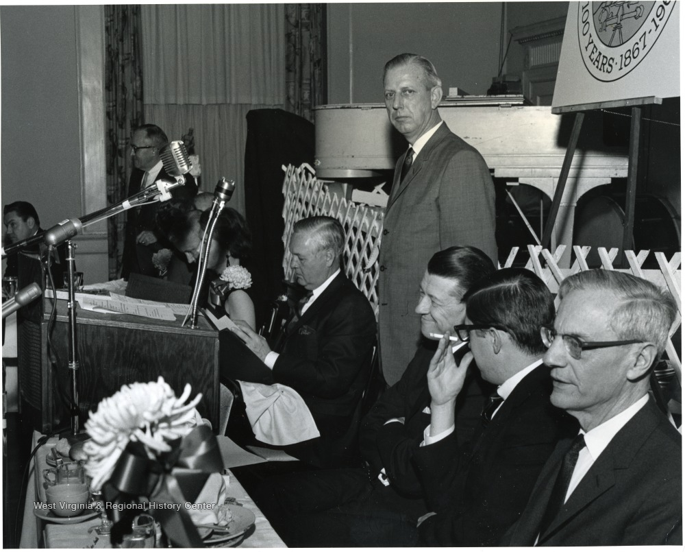 'Part of head table at Feb. 13, WVU Birthday Dinner.  From left to right: those identifiable include: Elvis Stahr, president of Indiana University and former WVU President; Dave Jacobs, executive secretary of WVU Alumni Association; Congressman Arch Moore; Mrs. Thomas White, Governor Hulett Smith; Thomas White, president of the Alumni Association; Dr. Harry B. Heflin, Acting WVU president; Jack Canfield, aide to Governor Smith; and Irvin Stewart, past president of WVU.'