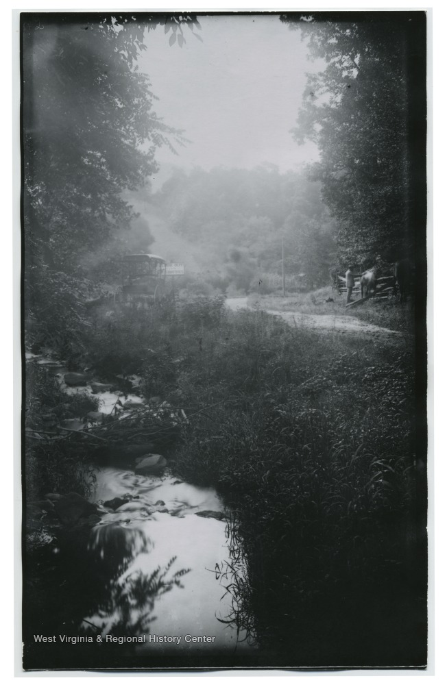 A small creek meanders through the photo.To the side is a man petting a horse. A buggy is parked by a sign that read 'Look Out for Locomotives.'  (80)D.I.C 138 appears on the back of the photo.