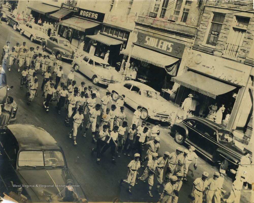 Little League teams parade down High Street past Rogers' Jewelry Store,and Sidler's Department Store.