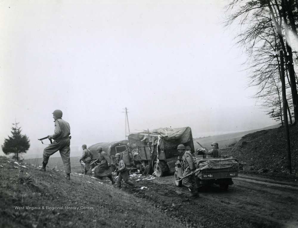 U.S. soldiers move on from a destroyed transport vehicle on the road as one G.I. mans a mounted machine gun in the jeep.
