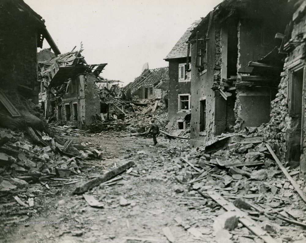 A lone soldier walks around the destroyed buildings in a German town towards the end of the war.