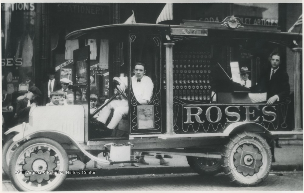 An unidentified man sits behind the wheel of an automobile advertising the store located on Temple Street and 3rd Avenue.