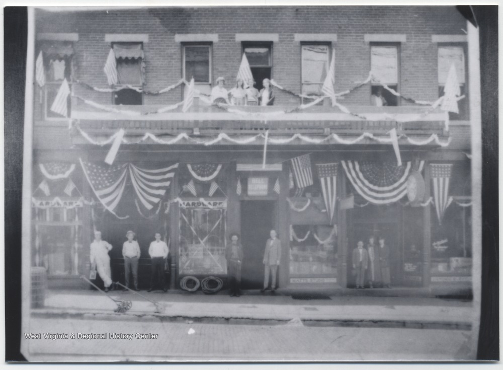 Unidentified people are lined up against the building, which is covered in American flags, located on the corner of Third Avenue and Temple Street.