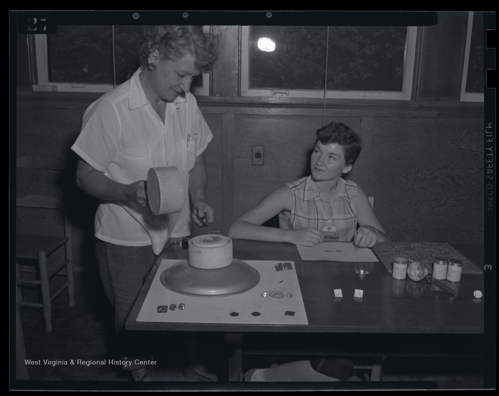 A young girl and woman making earrings. Subjects unidentified.