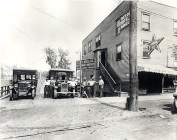 "Exterior of Star Bus Company featuring employees posing for portrait with two buses; routes to Cassville and Maidsville are advertised; company office and the ""Reed Hotel Annex"" are in same building.<br />"