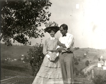 Young couple standing on top of a hill; the woman is wearing a large hat.