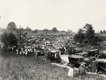 Celebration of completion of a highway project.  The picture features a crowd and numerous parked automobiles in the vicinity of a highway through a rural area in north central West Virginia.