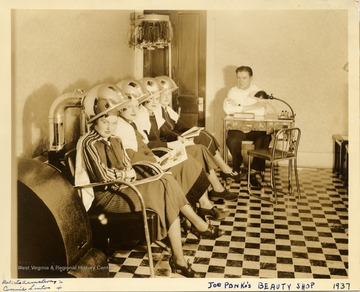 Four young women posing with hair dryers in Joe Ponka's Beauty Shop, Morgantown.  Roberta Armstrong is second from left; Connie Linton is fourth from left.