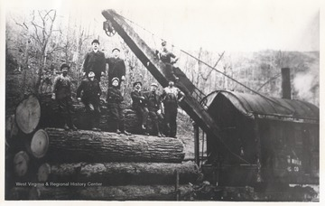 Logging crew posing on locomotive.