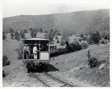 "Locomotive and passenger cars; Walter Good, conductor, on left side with hand on walkway chain; P.F. ""Bus"" Long, C&O station agent, to Walter's right, also with hand on chain; photograph from Richard Carter, N. White Hall Rd., Norristown P.O. 3 P.A."