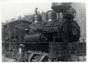 Ivan Clarkson standing next to train engine. Sunday afternoon; Ivan Clarkson Collection.