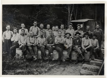 Group portrait of men sitting on a wooden bench.<br />
