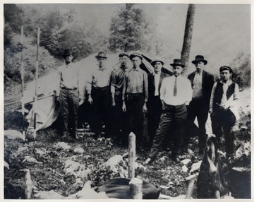 Group of men pose at their camp site. None are identified.