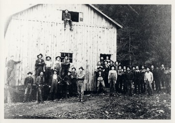 Group portrait of lumber workers in front of building.