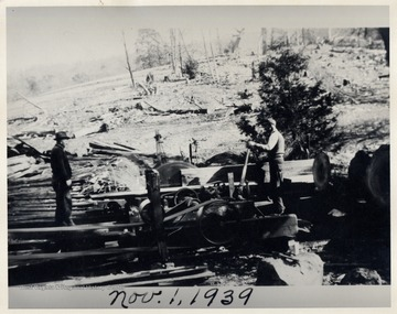 Two men using lumber machinery next to a timbered hillside.  Pendleton Co.