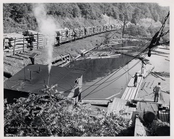 Men direct floating logs on the pond as a log train passes.