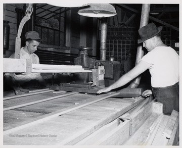 Two men cutting wood.  L to R  1. Arthur White  2. Marvin Moss