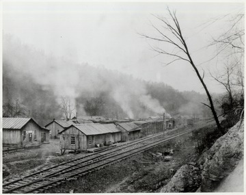 Wooden buildings next to train tracks.