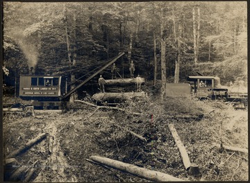 Log Loader and train engine transporting lumber. Four men standing on logs.