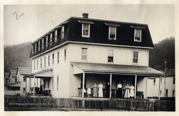 Group of people standing on the porch of the Meadow River Lumber Company Boarding House, Rainelle, W.V.