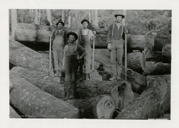 Four men standing on logs.  Preston Moore on left.