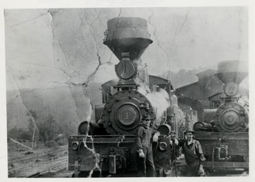 Two train engines and two men in front of them.