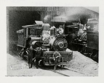 Three men in front of a train engine.