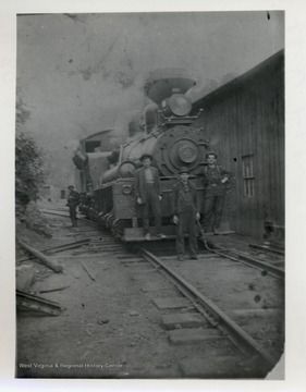 Men standing on and in front of train.  One man off to the side in the back.  Original from C.B. Cromer.