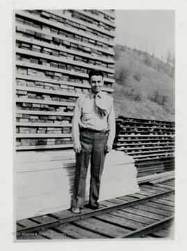 Ray McClelland standing in front of a lumber pile on a train track.