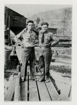 Two men standing on lumber at a log pond.  Original from Paul James.