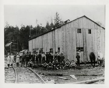 Large group of men in front of a building beside a railroad track.
