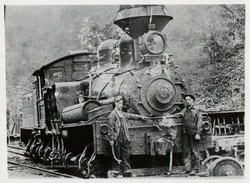 Train engine with two workers in front of it.