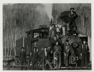 Train engine with crew standing in front and top of it.
