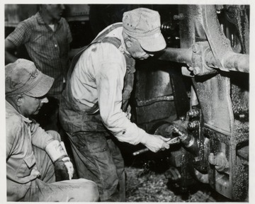 Walter Good applies wrench to the grease cups lubricating the side rods of his engine before going up on the Mt. while fireman, Paul Bradley looks on.  Both were veterans of log hauling days before passengers where hauled on Cass Scenic Railroad.