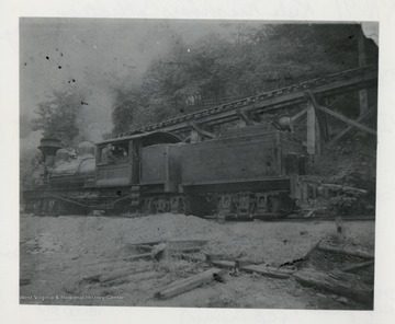 Side view of Shay train engine beside a trestle.  Original from C.B. Cromer