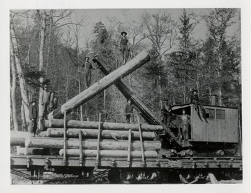 Nine men standing on logs and a loader of a railroad car.