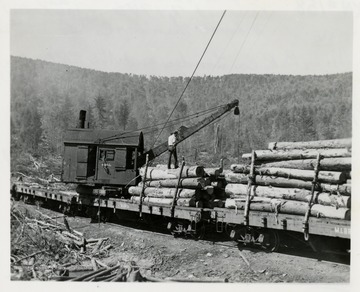 Loader putting lumber on cargo cars.  Man standing on logs on the car.