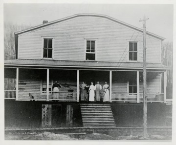 Group of women on porch, possibly a hotel or boarding house.
