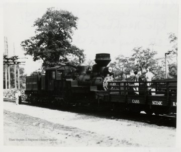 Side View of Shay train engine pushing a cart with two men on it.