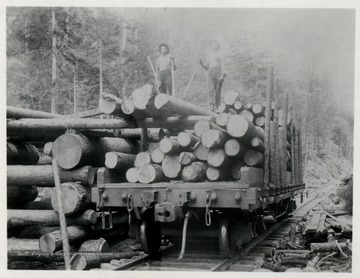 Men stand atop logs in car on tracks. Appears to be Narrow Guage.