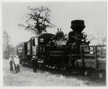 Side view of Shay train engine.  Four men standing beside it.  Clyde Galford, Engineer.