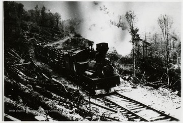 Shay engine with log cars traveling along hillside.