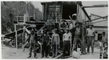 Group portrait of lumber crew, mill in background.
